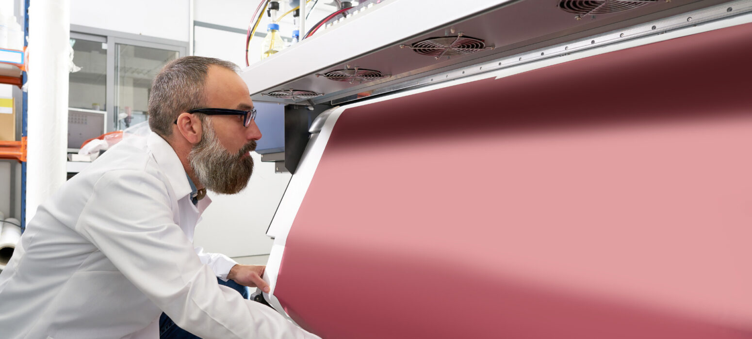 Man using a printer blanket coating machine for large scale printing