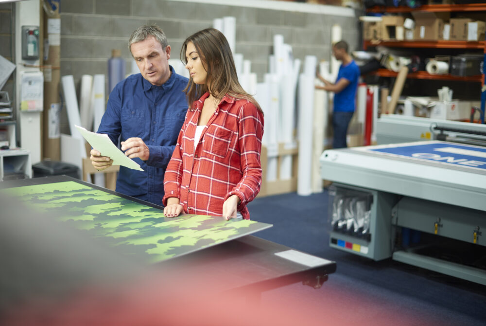 Male and female workers in a printing studio discussing design project