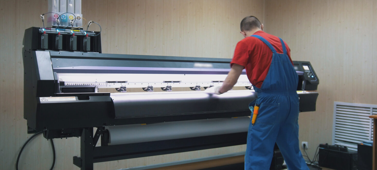 Male worker in blue overalls using large printing machine
