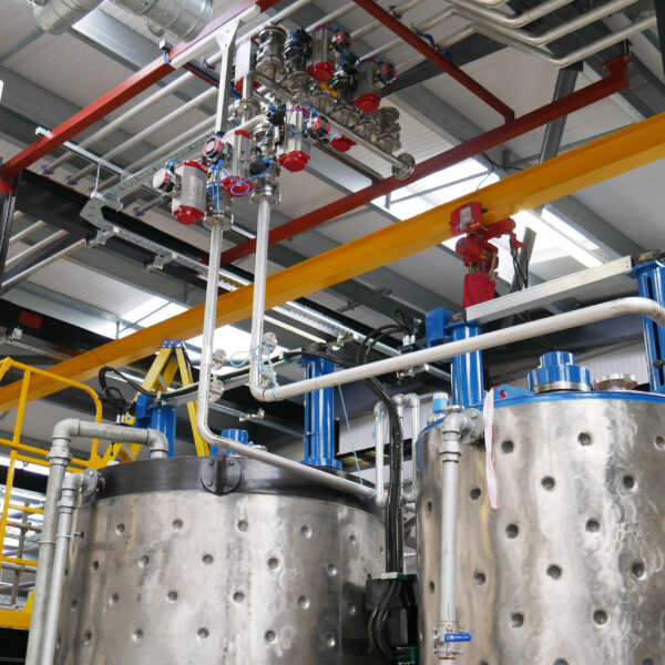 Factory product mixing machinery showing lots of pipework and dials