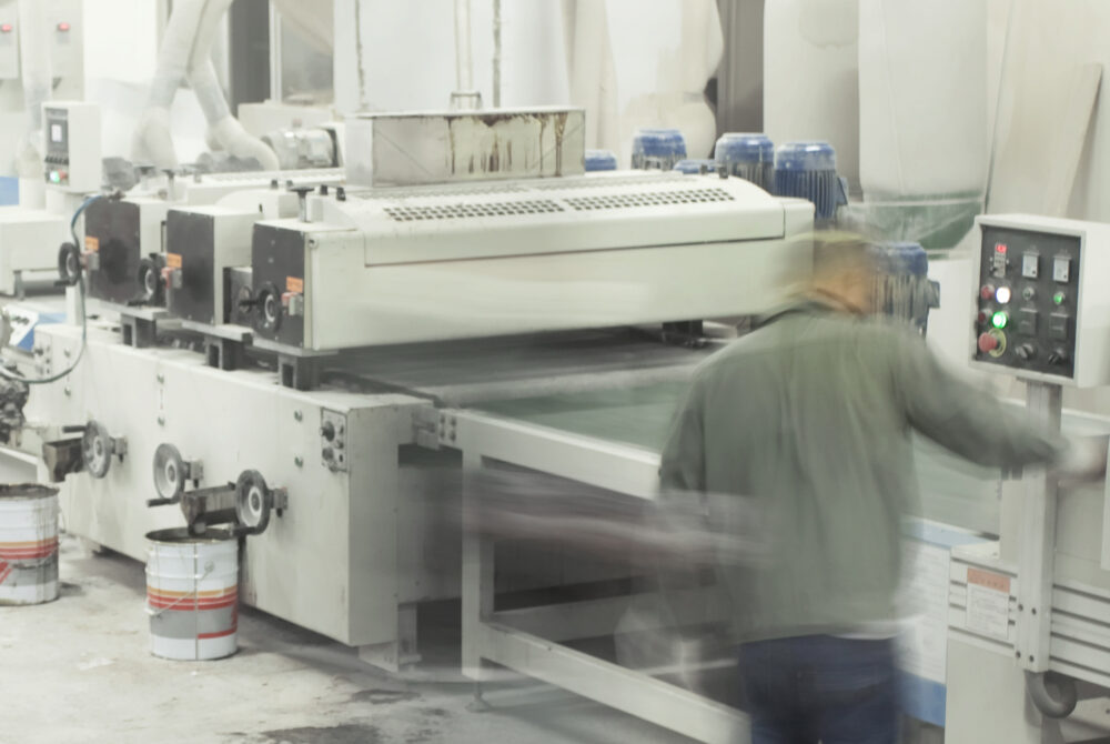 Blurred image of coating application machinery. Blurry emphasizing speed of process