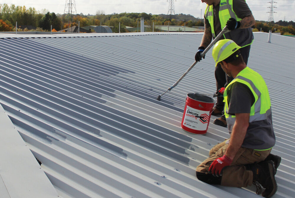 Two male roof workers applying a coating to a metal roof