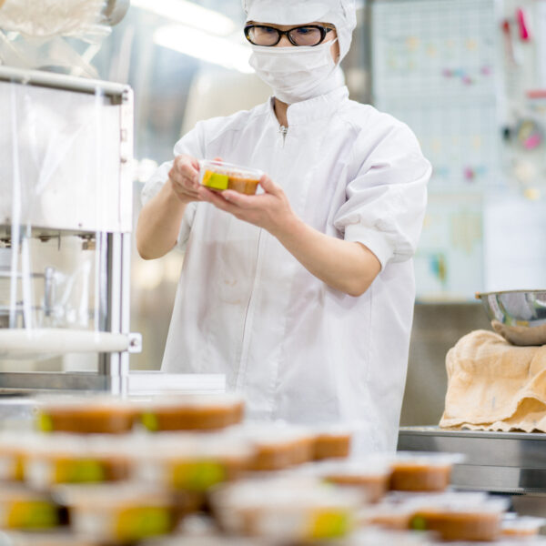 Worker in a food processing factory packaging food
