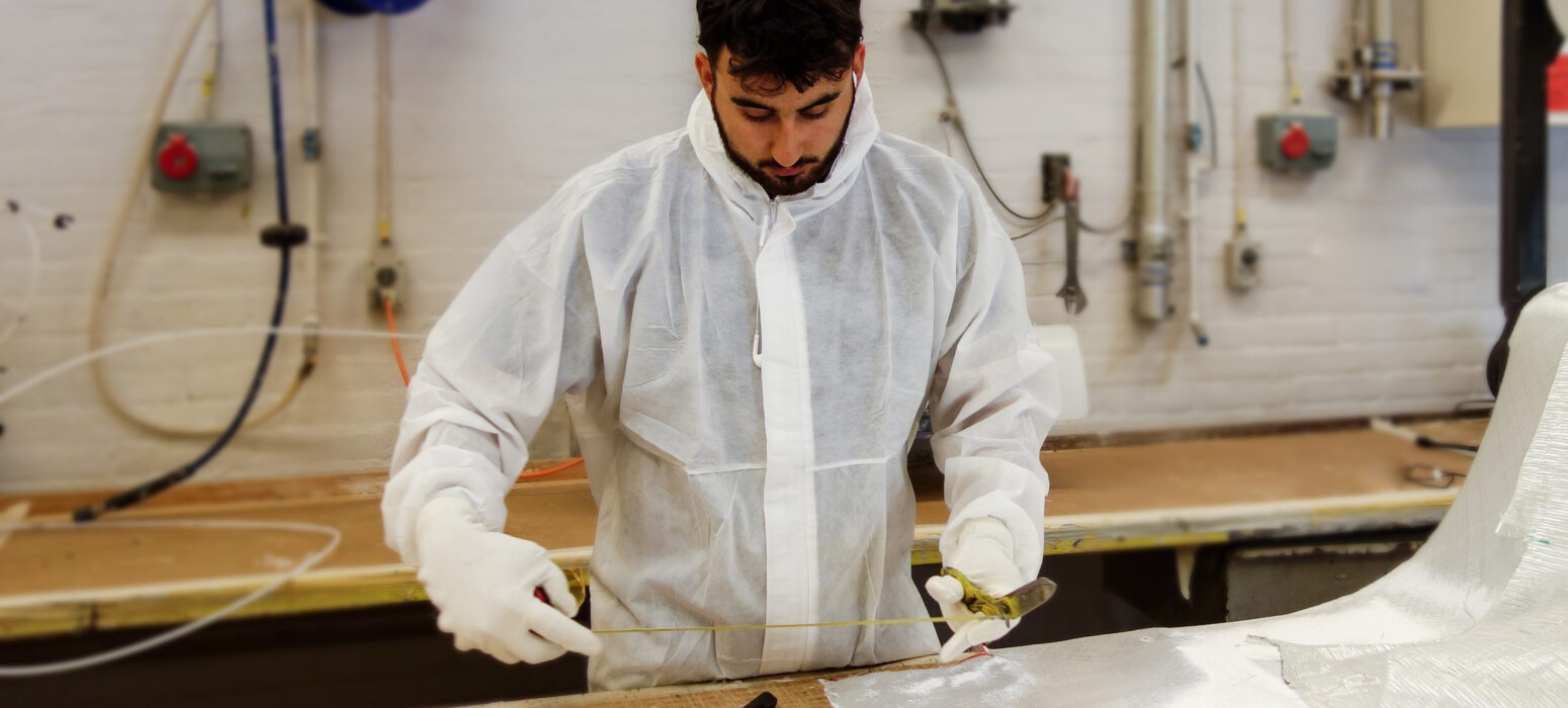 Man in protective equipment holding tape meter and preparing to cut fibreglass