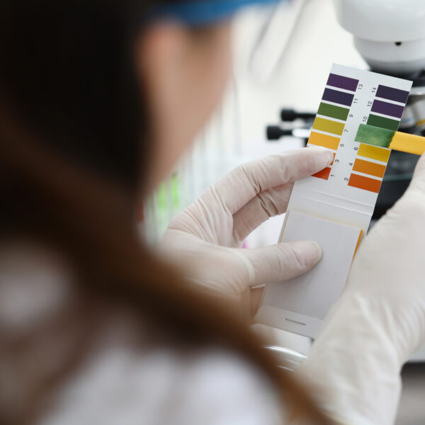Female lab worker doing paper litmus tests