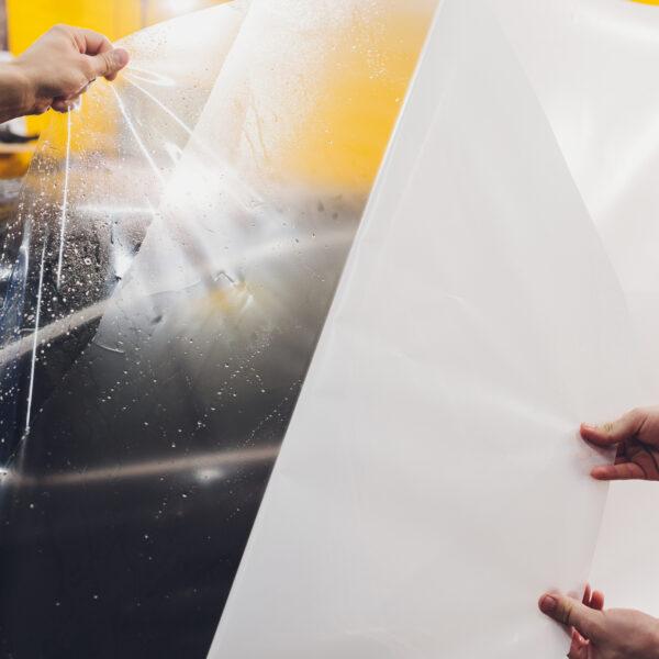 Transparent film being peeled off a black car