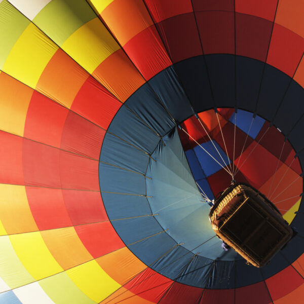 colourful hot air balloon from below showing bottom of basket
