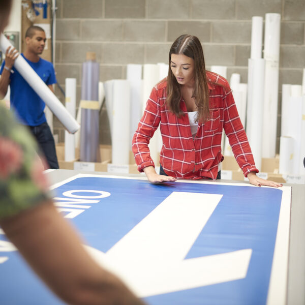 Young female working on a one way arrow sign product