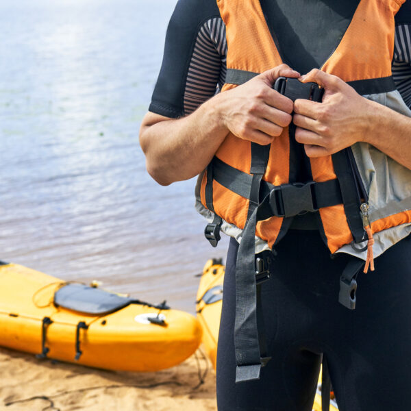 Man putting a life vest on with canoes and water in the background