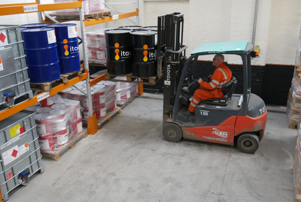 factory worker using a forklift truck to store large container barrels