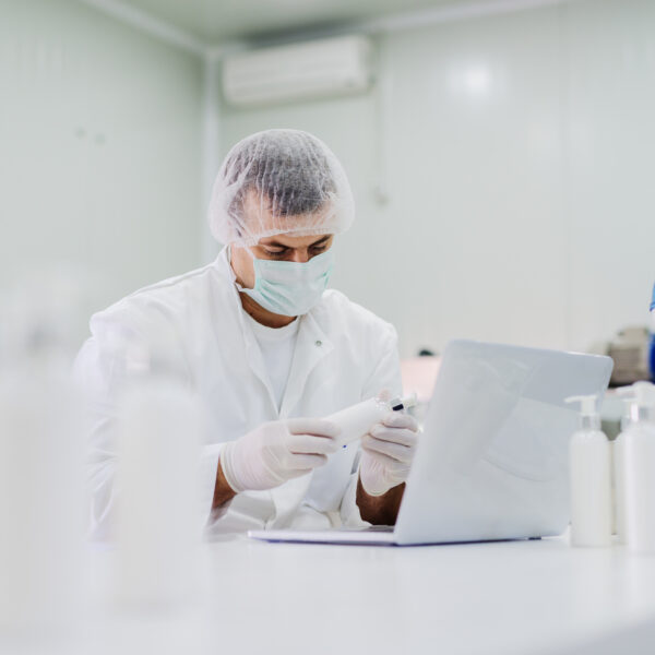 Man in white sterile clothes analysing results of a hand soap product