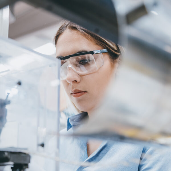 Female laboratory worker using equipment and with protective glasses