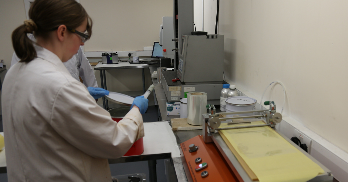 Lab Assistant working with draw down coater for testing