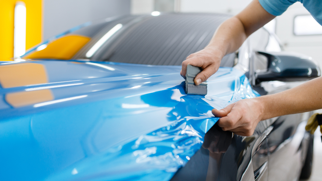 worker applying a blue car wrap to a black car