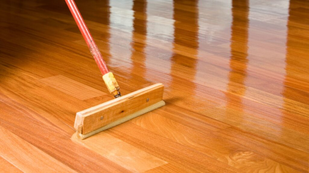 squeegee style brush applying polyurethane coating to a hard wooden floor