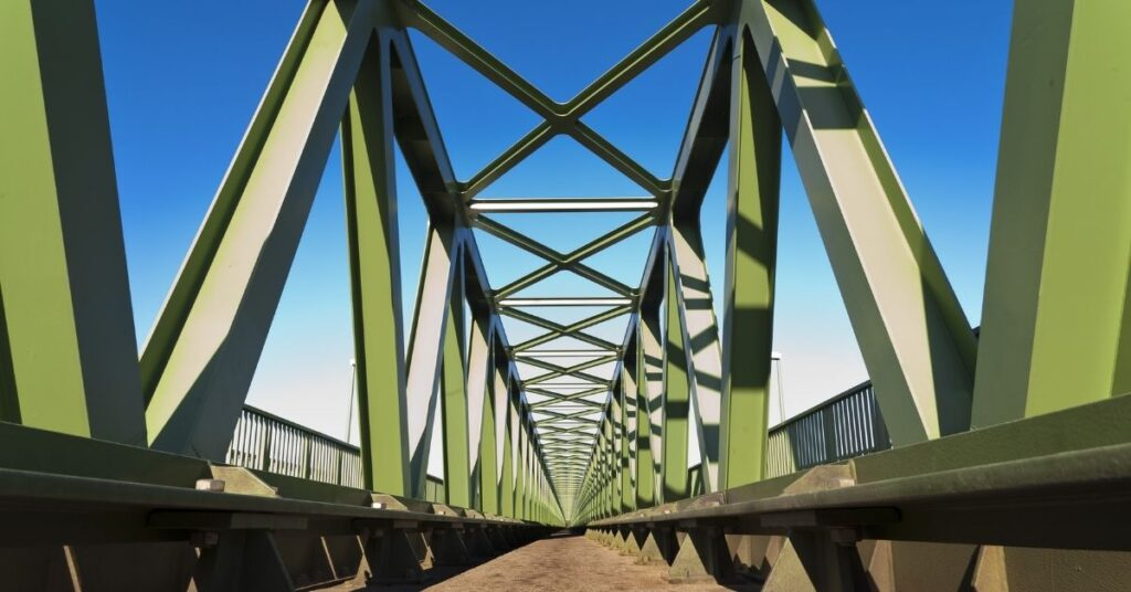 Metal structure of a large green bridge with blue skies in background